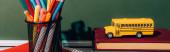 vodorovný obrázek modelu školního autobusu na knihách v blízkosti držáku pera s papírovou šablonou na notebooku v blízkosti zelené tabule