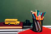 school bus model on staked books near pen holder with stationery on notebook near green chalkboard