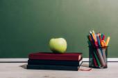 Reifer Apfel auf Büchern neben Stifthalter mit Schulmaterial auf Schreibtisch neben grüner Tafel