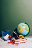 Globus in der Nähe von Schulbus Modell und Stifthalter auf Büchern in der Nähe von Lunchbox auf Schreibtisch in der Nähe von grüner Tafel