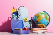 iskolai hátizsák tele levélpapírral közelében uzsonnás doboz, földgömb, iskolabusz modell és könyvek rózsaszín