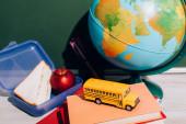 zeměkoule u oběda box a školní autobus model na knihách v blízkosti zelené tabuli