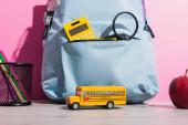 modrý batoh se školními potřebami u modelu školního autobusu, zralé jablko a držák na pera s plstěnými pery na růžové