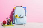 iskolai hátizsák tele levélpapírral közel másolókönyvek, alma és toll tartó filctollal rózsaszín