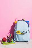 kék hátizsák iskolai kellékek közelében notebook, alma és toll tartó filctollal rózsaszín