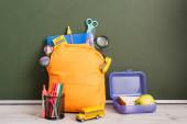 sárga hátizsák tele iskolai kellékek közelében ebéd doboz, iskolabusz modell és tolltartó az asztalon, közel a zöld tábla