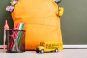 žlutý batoh u školního autobusu, držák na pera s plstěnými pery, nůžkami a děličem kompasu na stole u zelené tabule