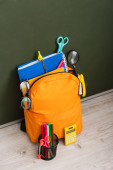 high angle view of yellow backpack with school supplies near calculator and pen holder