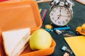 selective focus of lunch box with tasty sandwiches and ripe apple near vintage alarm clock and school supplies on black chalkboard