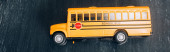 top view of yellow school bus model with stop sign on black chalkboard, horizontal image