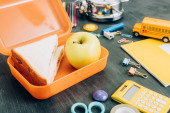 selective focus of lunch box with sandwiches and whole apple near school supplies on black chalkboard