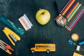 shora pohled na školní autobus model, celé jablko a školní celiny na černé tabuli