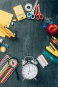 top view of frame with ripe apple, school bus model, vintage alarm clock and school supplies on black chalkboard