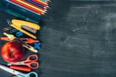 horní pohled na školní potřeby a zralé jablko na černé tabuli s kopírovacím prostorem