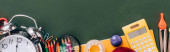 pohled shora na staré budíky poblíž školních potřeb na zelené tabuli, panoramatické plodiny