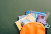 pohled shora na žlutý batoh plný školních potřeb na zelené tabuli