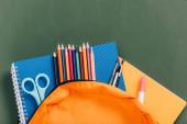 vrchní pohled na žlutý batoh s barevnými tužkami, sešity, nůžkami a štětci v blízkosti zelené tabulové desky