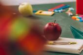 szelektív fókusz alma és iránytű elválasztó könyv közelében iskolai kellékek zöld táblán