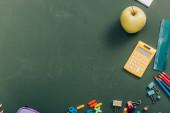 top view érett alma és számológép közelében iskolai kellékek zöld táblán