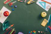 top view keret iskolai kellékek, érett alma és papírhajó zöld táblán