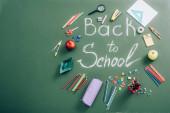 pohled shora na školní potřeby a celá jablka v blízkosti školní nápisy na zelené tabuli