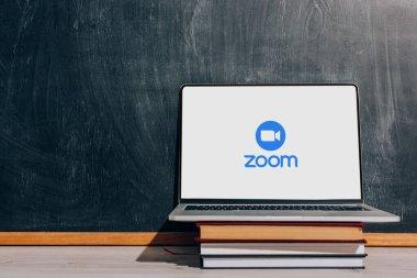 KYIV, UKRAINE - JULY 7, 2020: Laptop with Zoom website on stacked textbooks near black chalkboard