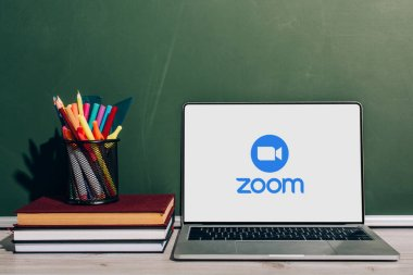 KYIV, UKRAINE - JULY 7, 2020: Laptop with Zoom website near pen holder with stationery on stack of books near green chalkboard