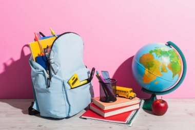 Blue backpack with school supplies near globe, books, pen holder, fresh apple and school bus model on pink stock vector
