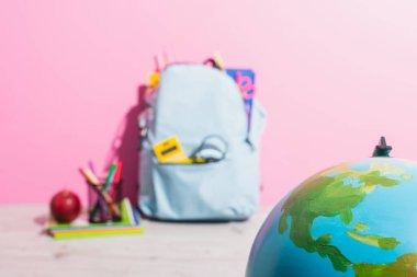 Selective focus of globe near backpack packed with school stationery, pen holder and ripe apple stock vector