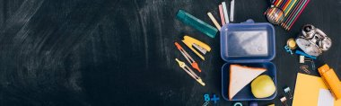 website header of lunch box with apple and sandwiches near school stationery on black chalkboard, top view