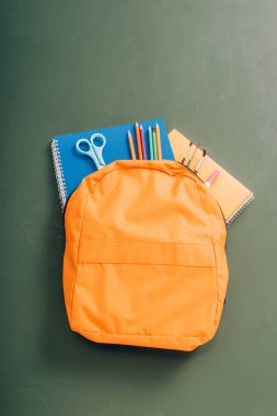 Top view of yellow backpack with copy books, scissors, color pencils and paintbrushes on green chalkboard stock vector