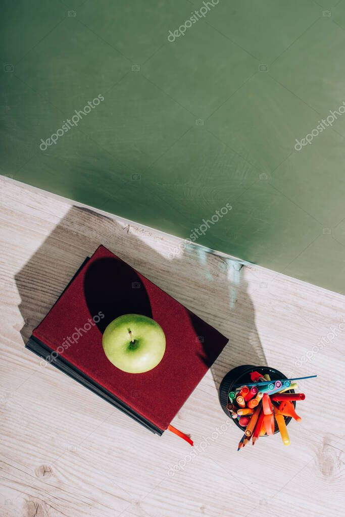 High angle view of whole apple on books near pen holder with stationery on desk near green chalkboard stock vector