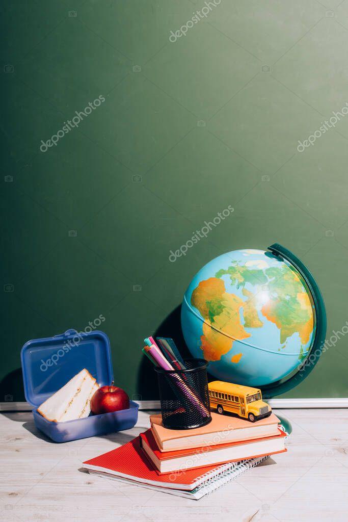 Globe near school bus model and pen holder on books near lunch box on desk near green chalkboard stock vector