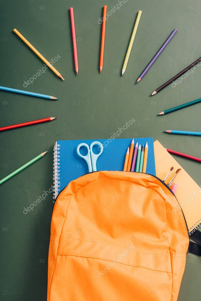 Top view of yellow backpack with school supplies near color pencils on green chalkboard stock vector
