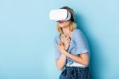 junge und verängstigte Frau im Virtual-Reality-Headset auf blau