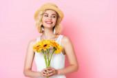 Frau mit Strohhut und weißem Kleid mit Blumen auf rosa