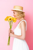 side view of woman in straw hat and white dress smelling yellow flowers on pink