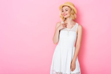 Woman in straw hat and white dress standing on pink stock vector