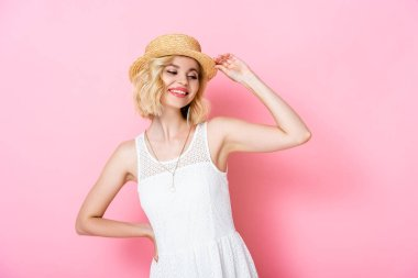 Young woman touching straw hat and standing with hand on hip on pink stock vector