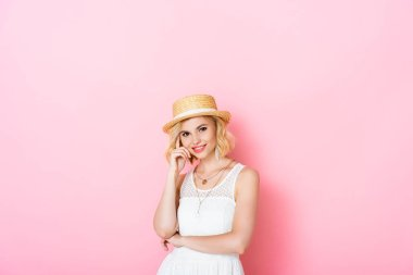 Young woman in straw hat looking at camera on pink stock vector
