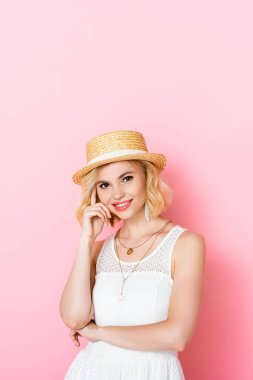 Young woman in straw hat touching face on pink stock vector