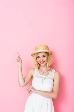 Young woman in straw hat pointing with finger while looking at camera on pink stock vector