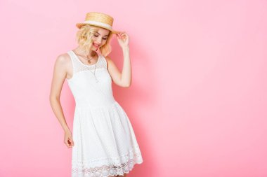 Young woman in white dress touching straw hat and looking down on pink stock vector