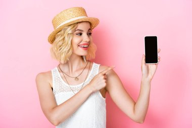 Woman in straw hat pointing with finger at smartphone with blank screen on pink stock vector