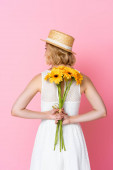 back view of woman in straw hat and white dress holding yellow flowers behind back on pink