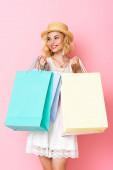 žena v slamáku a šaty drží nákupní tašky na růžové