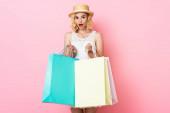 překvapená žena v slamáku a bílé šaty drží nákupní tašky na růžové