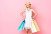 elégedetlen nő fehér ruhában és szalma kalap gazdaság bevásárló táskák, miközben álló kézzel csípő rózsaszín