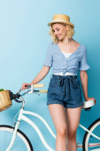 woman in straw hat standing near bicycle on blue