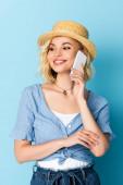 Frau mit Strohhut redet auf Smartphone auf blau